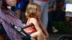 Girl seats in baby stroller. Entertainment park (Editorial) Stock Footage