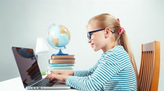 Schoolgirl child 7-8 years using credit card and her laptop and smiling Stock Footage