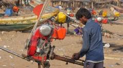 Man preparing engine of boat on beach,Konark,India Stock Footage