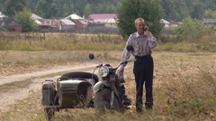 Russian Rural Area. Senior Man Having a Phone Call by His Retro Sidecar Stock Footage