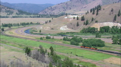 Freight Train Approaching Bend In Clark Fork River Stock Footage
