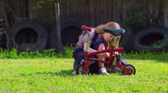 Girl repairs a bike on a sunny green glade Stock Footage