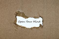 The word open your mind appearing behind torn paper Stock Photos