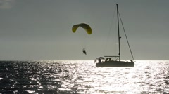 Motorized paraglider low pass near a sailboat Stock Footage
