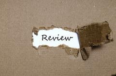 The word review appearing behind torn paper Stock Photos