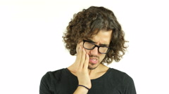 Toothache. Frustrated young man touching his cheek - stock footage