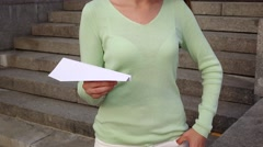 Young woman in light green blouse hold white paper plane in her hand Stock Footage