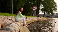 Dreamy woman with long hair sit on stony river bank at park, small waves splash Stock Footage