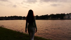 Girl come to river shore enjoy vivid and tender sunset, slow motion Stock Footage