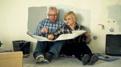 Senior couple talking and checking blueprints at their new home Stock Footage