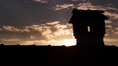 Silouhette of Chimney Like A Little House On The Roof in the evening twilight Stock Footage