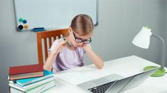 Schoolgirl 7-8 years doing homework in mathematics in her desk Stock Footage