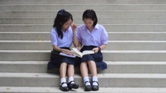 Thai high schoolgirls student couple in uniform sit on the stairway reading book - stock footage