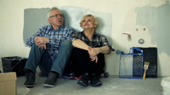Happy, mature couple talking and resting on floor at their new home Stock Footage