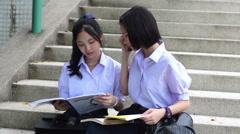 Thai high schoolgirls student couple in school sit on stairway discussing book Stock Footage