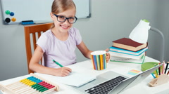 Portrait student girl 7-8 years doing homework and drinking tea from cup Stock Footage