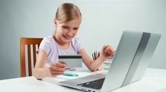 Portrait student girl 7-8 years using credit card and shopping online by laptop Stock Footage