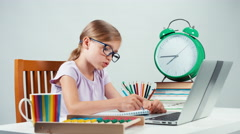 Portrait student girl child 7-8 years sitting in her desk and something writing Stock Footage