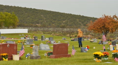 Man in  orange hoodie contemplates at grave on rainy Memorial Day Stock Footage