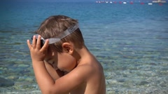 Cute boy takes off goggles and looks into camera Stock Footage