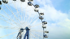 Ferris wheel rotates against the blue sky.  Stock Footage