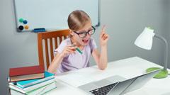 Schoolgirl 7-8 years something writing in her notebook in her desk Stock Footage