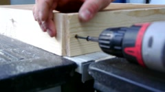 Man joins wooden planks using a power screwdriver Stock Footage