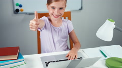Child girl 7-8 years using laptop in her desk and smiling at camera. Thumb up Stock Footage