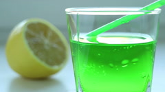 Green carbonated beverage of tarragon, green cocktail stick, lemon Stock Footage