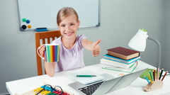 Portrait child 7-8 years looking at laptop and holding cup of tea. Thumb up. Ok Stock Footage