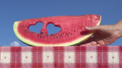 Female hand take a decorated watermelon slice with heart shaped holes on table - stock footage