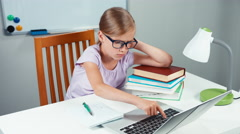 Portrait student girl 7-8 years doing homework  with laptop Stock Footage