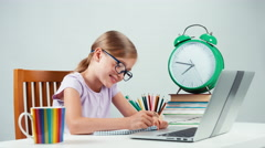 School girl child 7-8 years old doing homework with help of laptop Stock Footage