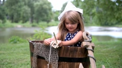Little Child Pretending to Fish Outside in Barrel - stock footage