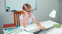 Schoolgirl doing homework in mathematics i her desk with help of laptop Stock Footage