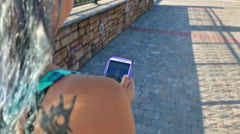 Funky girl plays Pokemon on smart phone on a cobblestone bridge Stock Footage