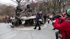 Tourists taking picture of Alice in Wonderland in Central Park Stock Footage