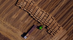 Aerial view of harvest fields with bale, tractor and forklift Stock Footage