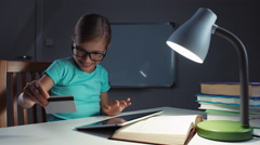 Portrait child 7-8 years old using credit card and tablet pc in the night Stock Footage