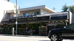 Uptown market on the street with cars passing - stock footage