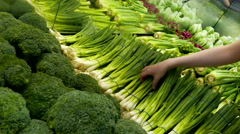 Woman selecting green onion in grocery store produce department - stock footage
