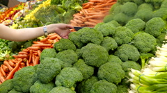 Woman selecting broccoli in grocery store produce department Stock Footage
