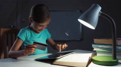 Child using credit card and tablet pc in the night. Child  gives to you card Stock Footage