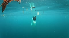 Plastic pollution problem. Bottles and bags dumped in sea causing environmental  Stock Footage