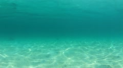 Underwater clip of sandy sea floor and blue ocean water Stock Footage