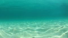 Underwater clip of sandy sea floor and blue ocean water - stock footage