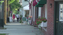 Main street in a small town as people walk around Stock Footage
