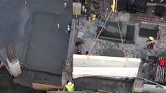 Construction workers guides a structural precast concrete into place Stock Footage