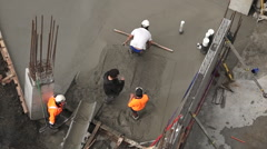 Construction site workers leveling cement in building site Stock Footage