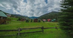 Clouds form over mountains as camera slides across fence Stock Footage